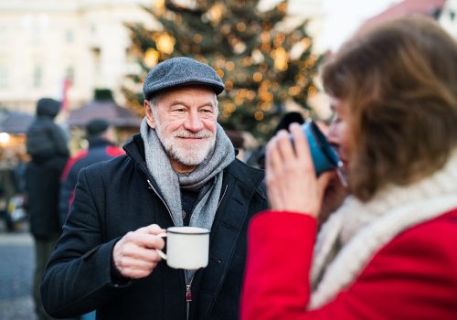 Happy senior couple on an outdoor Christmas market, drinking tea or coffee. Winter time.